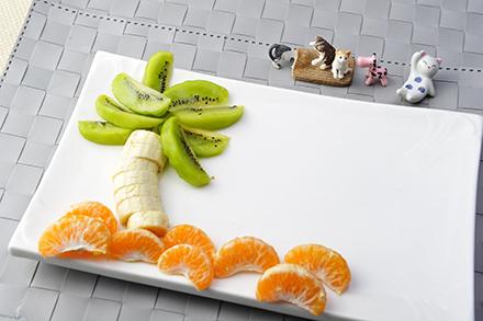 切好奇异果,香蕉和橙,摆成椰树的形状.