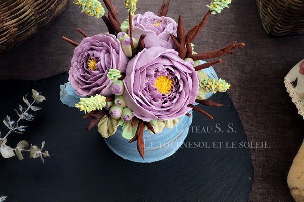 6. 接下来裱花啦!虽然此蛋糕就用了两种花,但做起来还是比较麻烦的。 紫色花:用10号挤一个粗壮的花蕾,1号挤花蕊;81号挤两层花瓣,80/81号再挤两层;103号挤弧形花瓣(2-3层);126号挤2-3层花瓣。 (花瓣每一层比上一层高且比上一层大一点。裱花袋准备两个:一个调3色渐变色,另一个调2色浅一点的渐变色装126号嘴。)做好的花冷冻5min备用。 叶子:104号嘴直接在蛋糕上挤叶子打底,可变换花嘴方向来调节叶子的颜色。 摆上冷冻好的花朵。 黄绿色小花:349号绿色直接在小树枝上从上至下的挤,用1