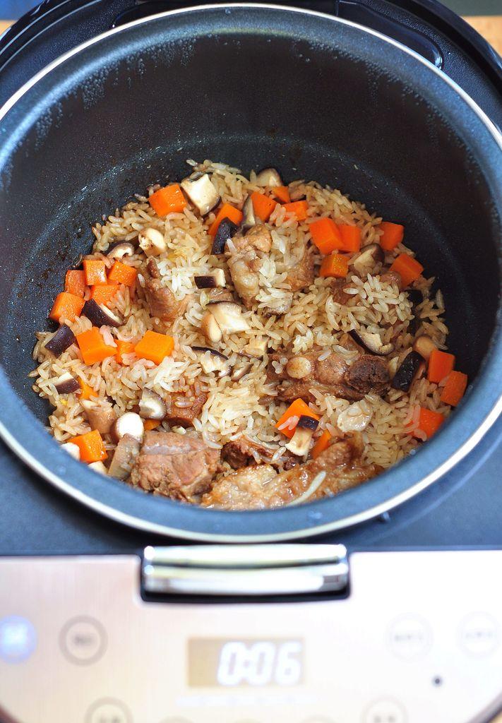 胡萝卜丁,香菇丁倒入电饭煲中,加适量的水,再用一个快煮饭程序,将米饭