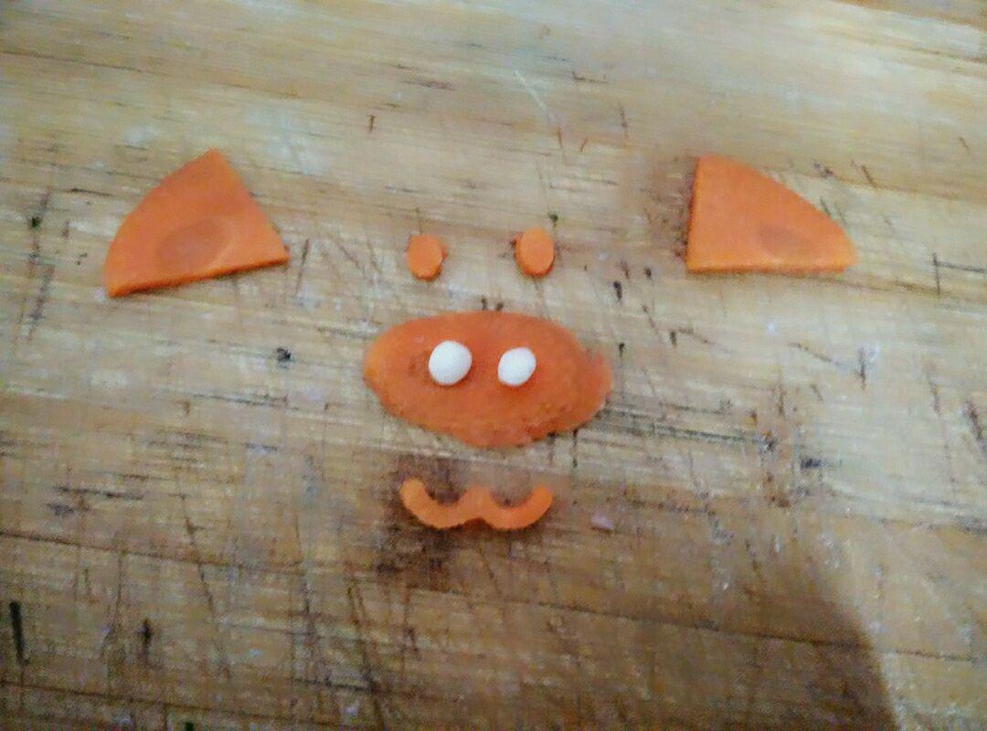 取一根胡萝卜切片,然后用刀刻成类似猪猪的眼睛鼻子