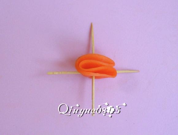 拿一片胡萝卜片对折,用牙签十字形状固定插起来
