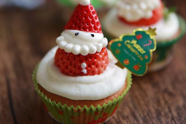 6. 先在蛋糕上面挤一层淡奶油,草莓去蒂,从三分之一处切开,把底部放在奶油上面,在草莓的上面挤一坨奶油,上面盖上草莓的顶部当作圣诞老人的帽子,在用小的圆孔裱花嘴挤上胡子和帽子上的圆球,用黑芝麻装饰民眼睛(忘记拍照)