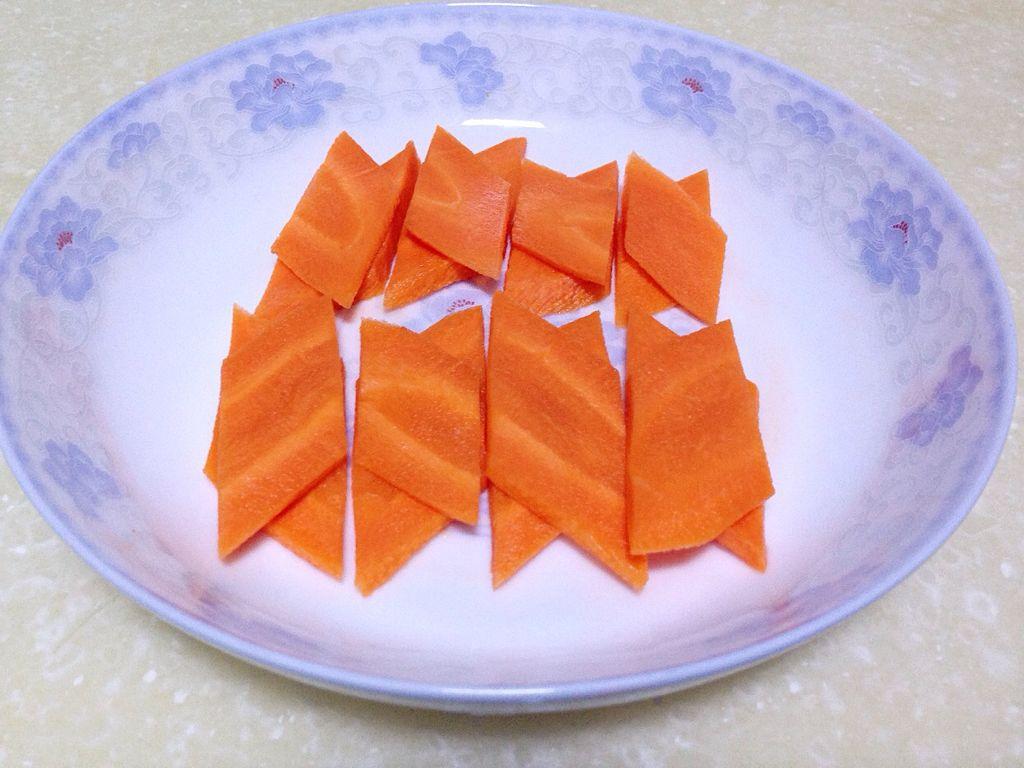 将胡萝卜去皮洗净,切菱形片(菱形片的切法:将整根胡萝卜斜刀切段,将
