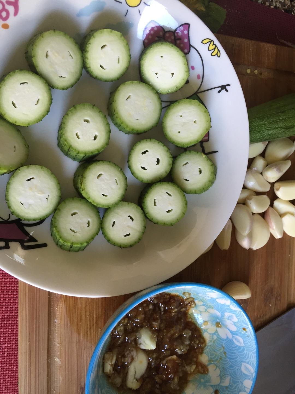 图解 丝瓜/1. 蒜压成泥,用香油生抽拌匀。丝瓜切片。