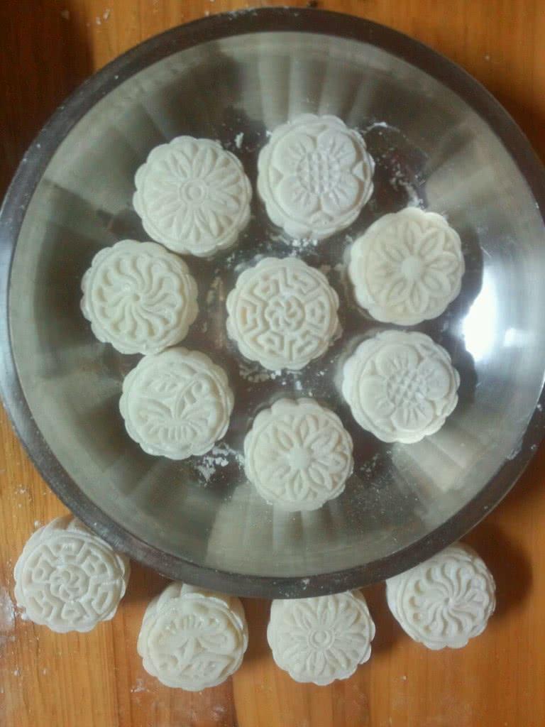 7. 蒸好的粉用汤匙挖松,放凉,带个一次性手套或者套个保鲜袋,把蒸好的粉浆揉均匀揉成团,直接带着一次性手套或保鲜袋弄点粉出来捏些面出来,放到铺有熟糯米粉的地方,然后手粘粉,搓成汤圆大小备用,把馅也按粉搓出来的数量搓成汤圆大小备用。我的模是10头50g的,这些粉能做12个月饼,比较小。