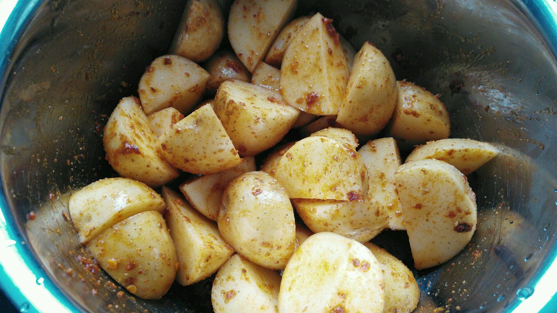 然后将小土豆切块,放入红油辣椒,盐,花椒粉把土豆拌好.