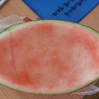 (取半个西瓜用刀把红色的肉切出来,切成小块,做成西瓜拼盘.)