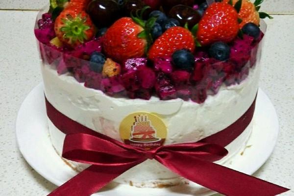 9. 准备好水果:红心火龙果一个,车厘子七八颗,奇异果一个,金桔一个,草莓十个,蓝莓十几个。把蛋糕剖成两部分,中间抹好奶油,可以加入水果, 我没加,把水果都放在了蛋糕表面。再把两片蛋糕放到一起,抹平奶油。用慕斯围边把蛋糕围好,我的慕斯围边是6厘米的,因为蛋糕太高,所以围了上下两层,再用丝带系好。火龙果,奇异果切小块平铺到蛋糕上。